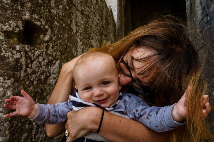 A mother with black-rimmed glasses kisses her baby's ear as he smiles at the camera and grabs a piece of her hair.